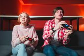 Couple Sitting On The Sofa With Gamepad In Their Hands And Playing The Game On The Console. Man And  poster