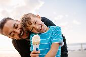 Boy Eating An Ice Cream Standing Near Seafront With His Father. Little Boy Holding An Ice Cream Cone poster