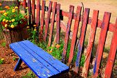Blue Bench And Red Fence