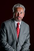 Studio Portrait Of An Older, Handsome, Latino Business Man.  He Is Leaning In Front Of A Dark Red Ba poster