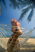Leisure in summer - Beautiful Tanned legs of sexy women. relax on hammock at sandy tropical beach.  poster
