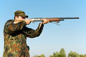 Male hunter in camouflage clothes on the field aiming the hunting rifle during a hunt.