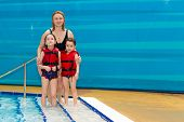 Little Girls With Her Mom Having Fun In Swimming Pool. Child Learns To Swim. Teaching A Child To Swi poster