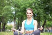 Girl Meditates In Lotus Pose On Green Grass. Practicing Of Yoga At Summer Park. Portrait Of Young Pe poster