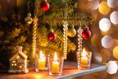 Burning Candles On Wooden Table Under Christmas Tree Decorated With Christmas Toys With Bokeh Lights poster