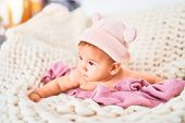 Adorable baby lying down over blanket on the sofa at home. Newborn wearing fanny hat relaxing and re poster