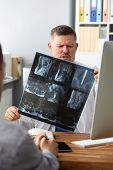 Portrait Of Serious And Concentrated Surgeon Looking Carefully At Spine X-ray In Different Projectio poster