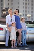 Beautiful father, mother and two children stand near convertible car; man laughs