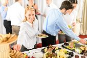 stock photo of buffet  - Business woman serve herself at buffet catering service company event - JPG