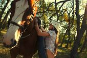stock photo of straddling  - Beautiful girl  straddling a horse in garden - JPG