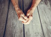 Elderly Woman Hands On Rustic Wooden Background. Senior Woman With Fingers Crossed. Wrinkled Palms S poster