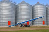 stock photo of auger  - A blue auger sitting in front of three steel grain bins 