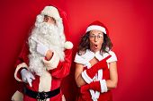 Middle age couple wearing Santa costume and glasses over isolated red background Surprised pointing  poster