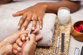 Close up of manicurist hands clipping client nails in a luxury spa. Young woman getting manicure tre poster