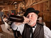 stock photo of chug  - Drunken man chugs a bottle of alcohol in a saloon - JPG