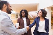 Happy Positive Business Partners Shaking Hands. Business Man And Women Standing In Office Hallway, S poster