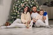 Beautiful Young Family Sitting Next To A Nicely Decorated Christmas Tree. Happy Family Having Fun Wi poster