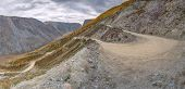 Picturesque Autumn Panorama With A Winding Dirt Rocky Road Through A Steep Pass, Part Of A Mountain  poster