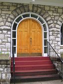 Arched Exterior Wood Door With Stairs Going Up.  Metal Kickplate On The Double Doors And Arch Glass  poster