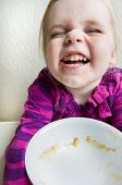 Child Finished With Her Bowl Of Healthy Food And A Messy Face