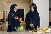 Two Arabian Women gathering cooking & drinking coffee in kitchen