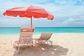 Pink umbrella and chairs on a beautiful Caribbean beach