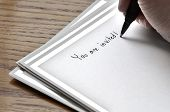 Person writing invitation on card with pen and ink
