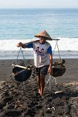 Traditional Sea Salt Production On The Volcanic Black Sand, Bali, Indonesia