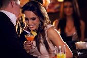 stock photo of flirt  - Happy couple at the bar enjoying the cocktail party - JPG
