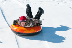 picture of inflatable slide  - Happy boy sleding on a tube down a hill - JPG