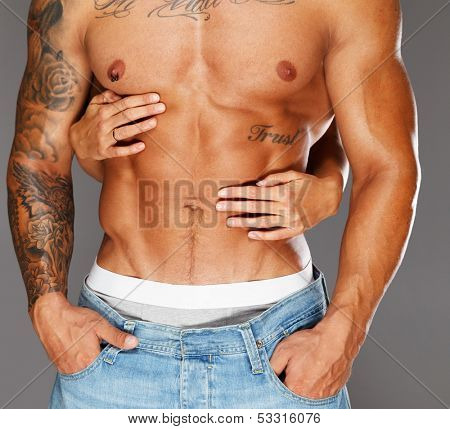 Woman's hands embracing man with naked muscular torso  poster