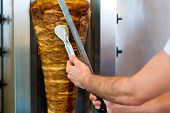 Doner kebab - friendly vendor in a Turkish fast food eatery, cutting meat with sharp knife in front