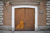 Stone Wall Of An Old Building With Old Weathered Wooden Gate With Peephole