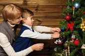 Happy mother and her lIttle boy decorating christmas tree in wooden house interior