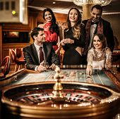 stock photo of gambler  - Group of young people behind roulette table in a casino - JPG