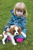 Young Girl Sitting With Puppy King Charles Spaniel
