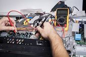 stock photo of capacitor  - Electronics Repair service with red probe and capacitors on electronic board - JPG