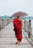 A monk walking on U Bein Bridge, Myanmar