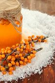 pic of sea-buckthorn  - Branches of sea buckthorn with jam and snow on wooden background - JPG