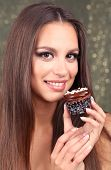 Portrait of beautiful young girl with chocolate cupcake on shiny background