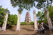 students ride bicycle in front of Thien Mu Pagoda