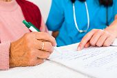 stock photo of nursing  - Nurse helping elderly with contract entering nursing home.