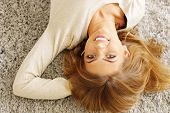 Young beautiful woman lying on the carpet at home