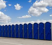 stock photo of porta-potties  - A row of blue portable toilets - JPG