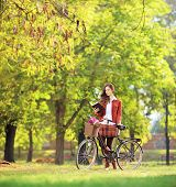 Young female with bicycle in a park reading a book, shot with a tilt and shift lens