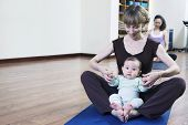 Mother and baby sitting cross-legged and doing yoga in yoga class