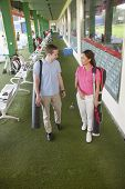 Young happy couple leaving  golf course with golf clubs and caddy