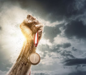 picture of gold medal  - Male hand rise up a gold medal against the dramatic sky with copy space - JPG
