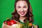 Young smiling woman with a fresh vegetables. on green background.