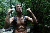 Muscular survivor man in jungle rainforest cheering aggressive. Strong male survival concept with gu